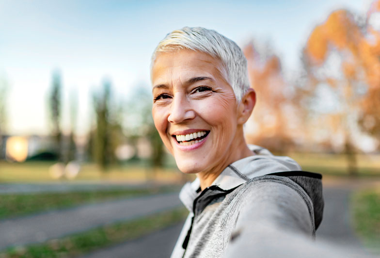 Smiling woman with short hair ready to learn more about Medicare options