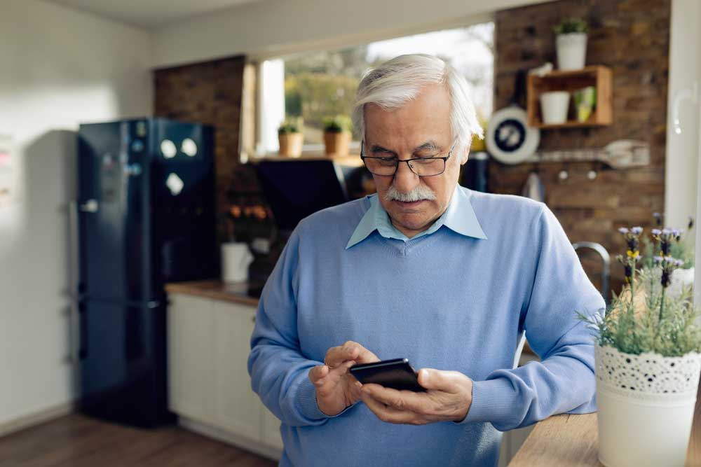 An elderly man reads on his phone and learns more about the three ways he can save on his Medicare costs