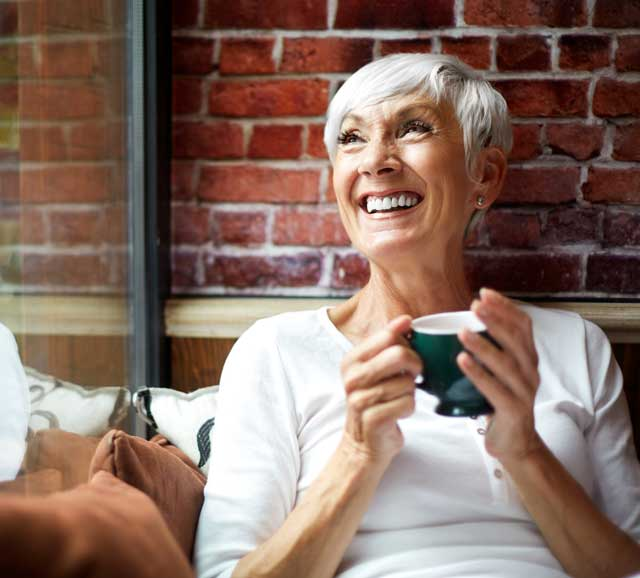 An older woman looks up smiling while drinking her coffee knowing she is covered with her Medicare Part C plan
